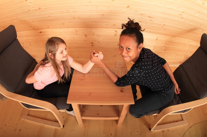 Arm wrestling. Girls trying arm wrestling - smiling Caucasian kid and young Papuan women sitting in armchairs in wooden attic room royalty free stock photography