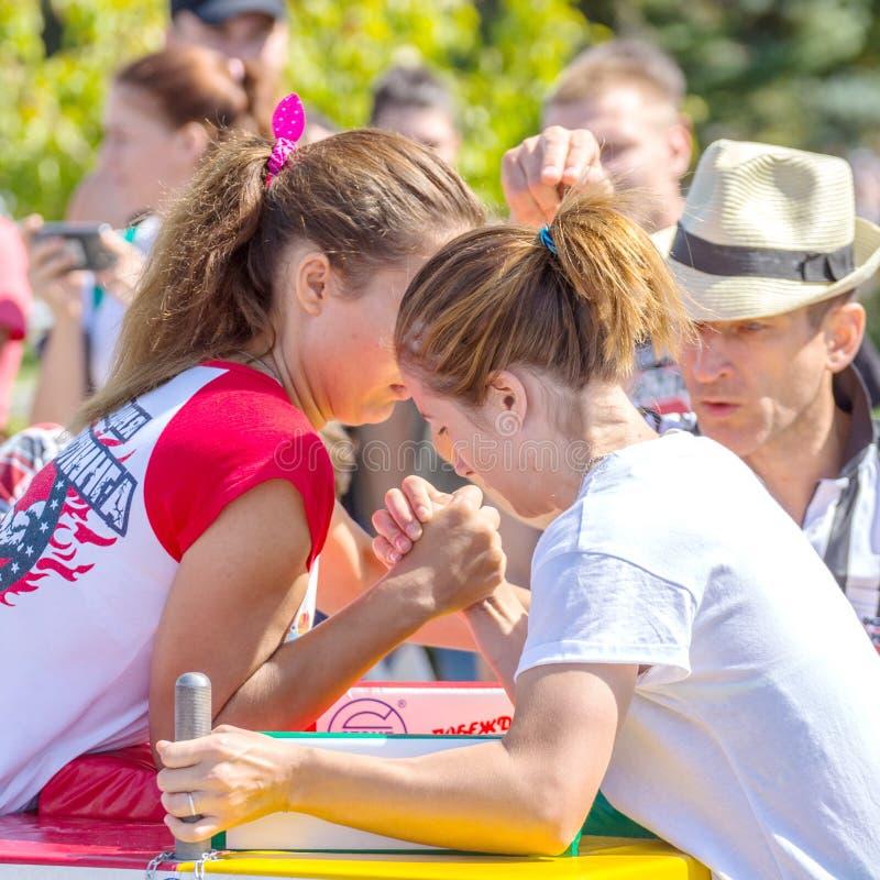 Arm wrestling among girls on the Volga River Embankment on a sunny summer day. Russia, Samara, August, 2018: arm wrestling among girls on the Volga River royalty free stock image