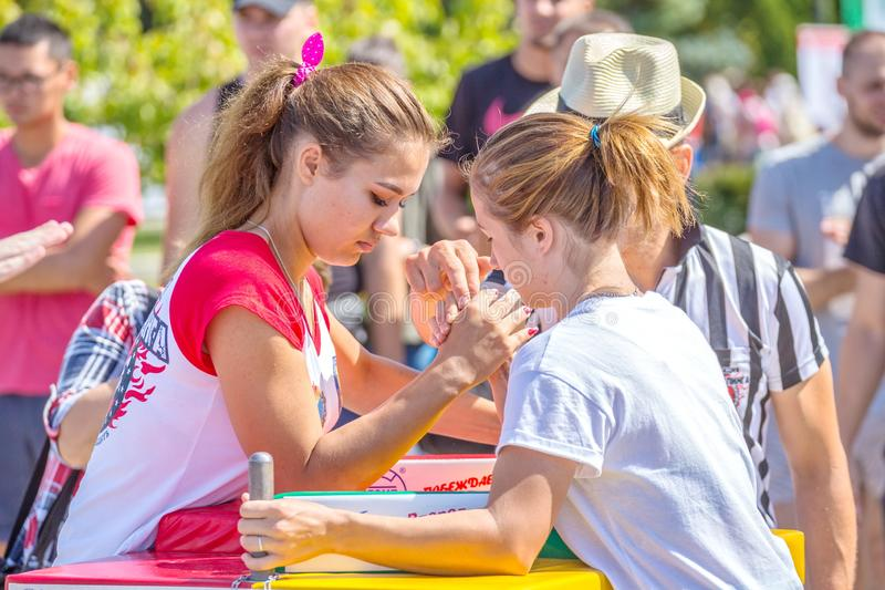 Arm wrestling among girls on the Volga River Embankment on a sunny summer day. Russia, Samara, August, 2018: arm wrestling among girls on the Volga River stock photo