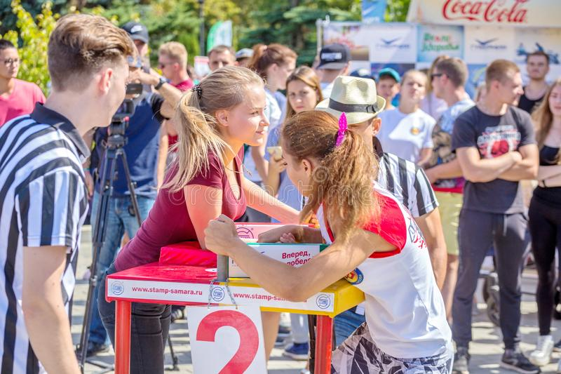 Arm wrestling among girls on the Volga River Embankment on a sunny summer day. Russia, Samara, August, 2018: arm wrestling among girls on the Volga River stock images