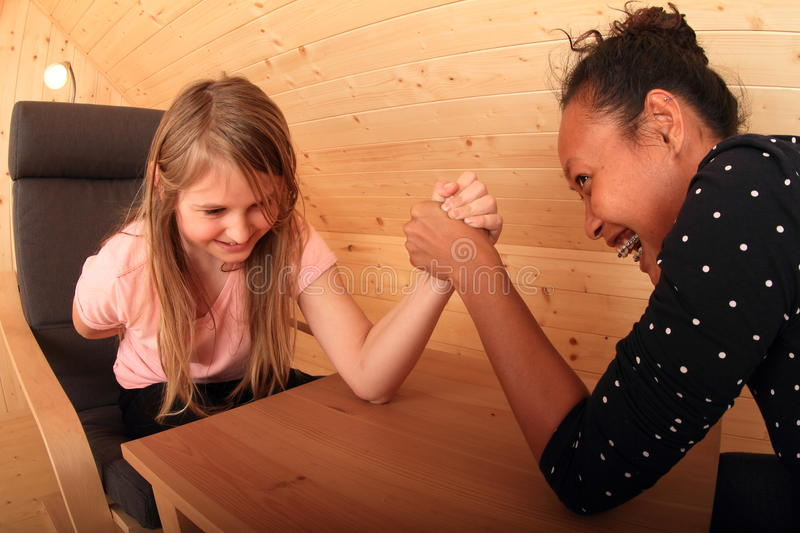 Arm wrestling - laughing girls. Girls trying arm wrestling - smiling Caucasian kid and laughing young Papuan women fighting on wooden table in attic room stock photos