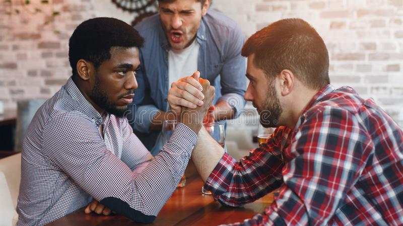 Arm Wrestling. Male Friends Having Fun In Bar royalty free stock photo