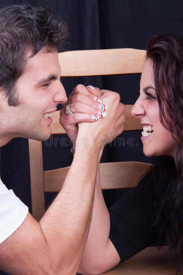 Arm wrestling. Between men and woman stock photography