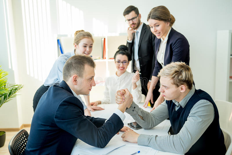 Arm wrestling in office. Between two workers royalty free stock photos