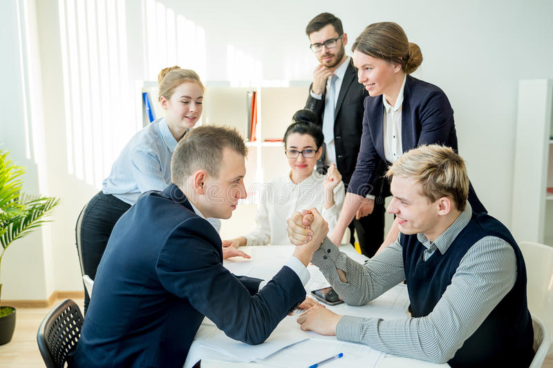 Arm wrestling in office. Between two workers royalty free stock image