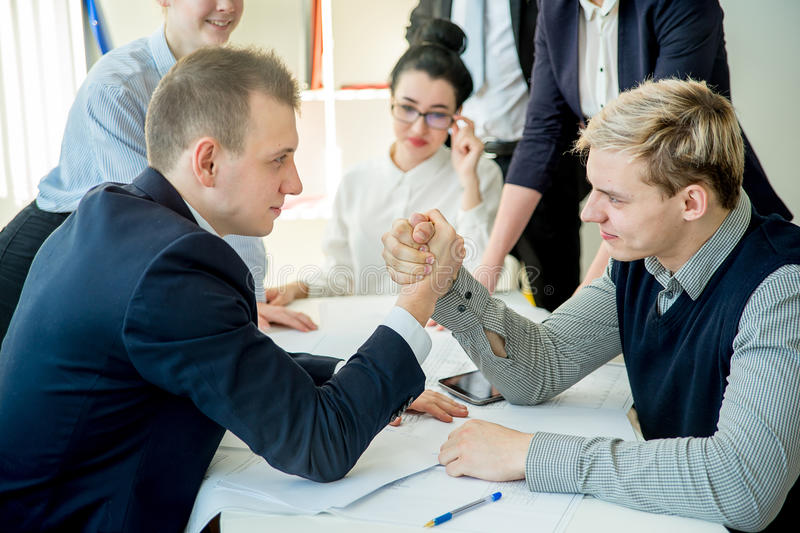 Arm wrestling in office. Between two workers royalty free stock images