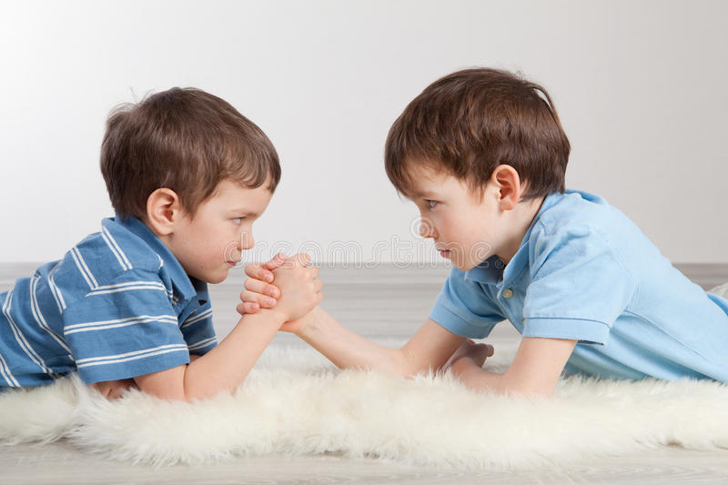 Arm wrestling and two brothers,. Indoor royalty free stock images