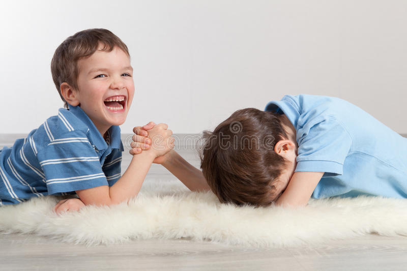 Arm wrestling and two brothers. Indoor stock photos