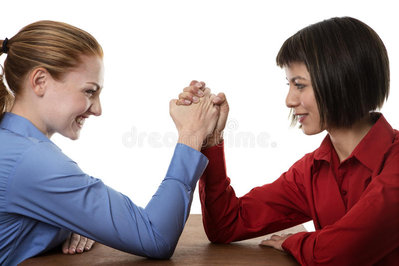 Arm wrestling. Two business women arm wrestling each other stock image