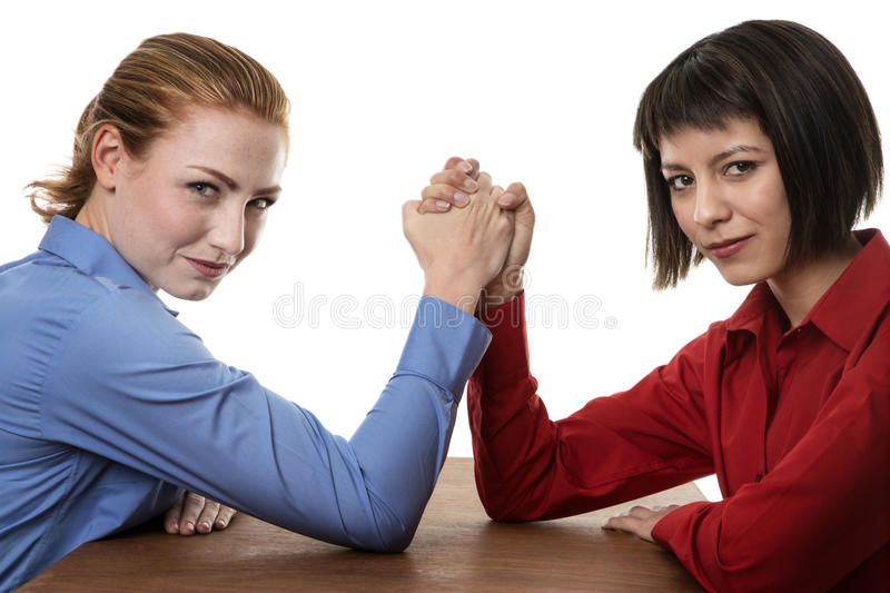 Arm wrestling. Two business women arm wrestling each other royalty free stock photos