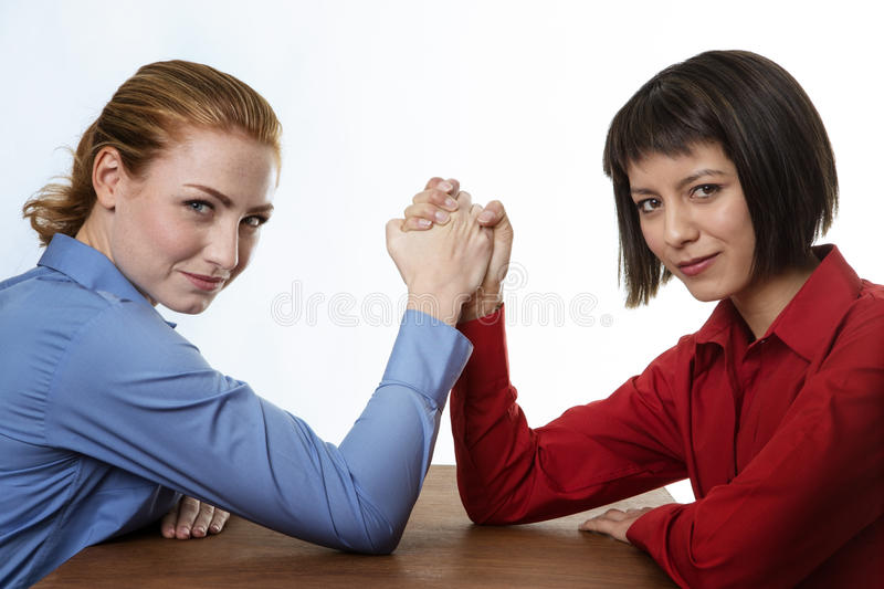Arm wrestling. Two business women arm wrestling each other stock photo