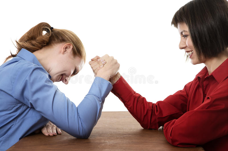 Arm wrestling. Two business women arm wrestling each other royalty free stock image