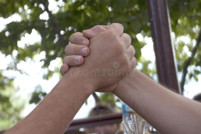 Arm Wrestling. Two men Arm wrestling on the outdoors royalty free stock photos