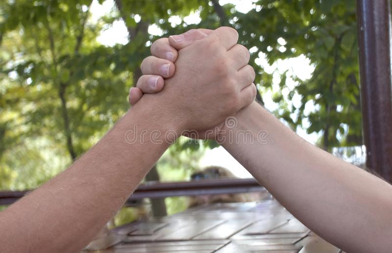 Arm Wrestling. Two people Arm wrestling on the outdoors stock images