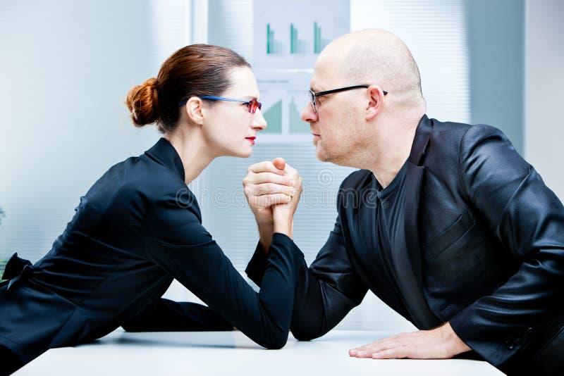 Arm wrestling woman VS man. Arm wrestling business women VS business man stock photography