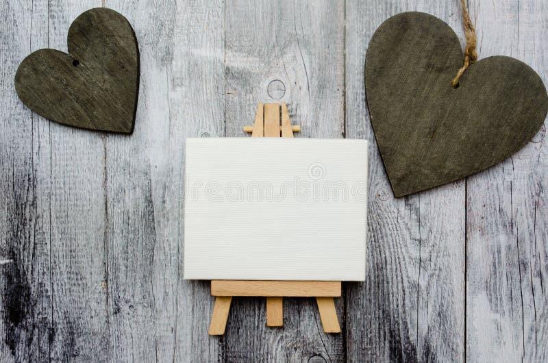 Armação pequena com uma lona vazia sobre os corações de madeira brancos e dois escuros Fundo de madeira velho e espaço grande da  fotos de stock royalty free