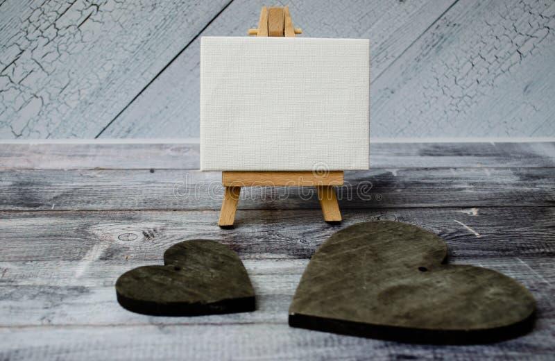 Armação pequena com uma lona vazia sobre os corações de madeira brancos e dois escuros Fundo de madeira velho e espaço grande da  fotos de stock