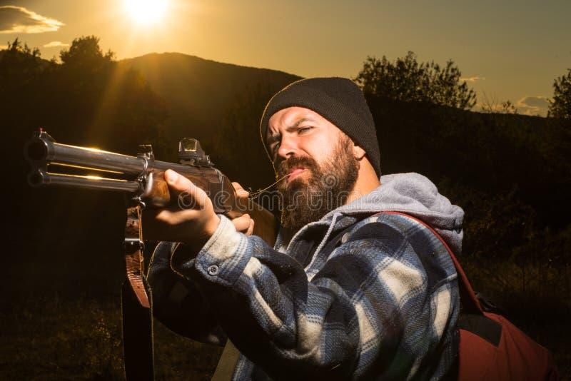 Arma barbudo de la tenencia del hombre del cazador y el caminar en el rifle Hunter Silhouetted del bosque en puesta del sol hermo fotos de archivo