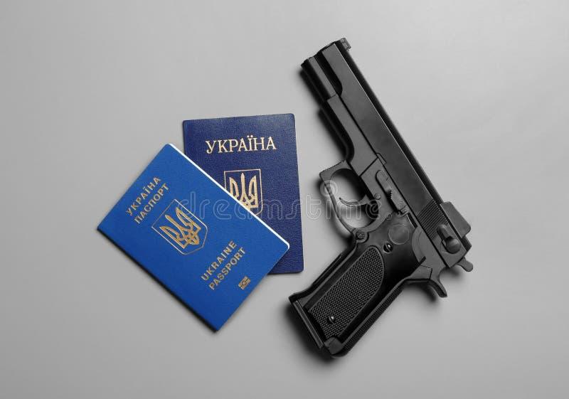 Arma com os passaportes ucranianos no fundo cinzento fotografia de stock royalty free