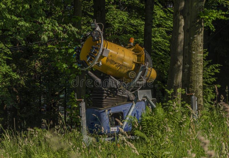 Arma da artilharia da neve no verão na inclinação verde do prado e do esqui fotografia de stock