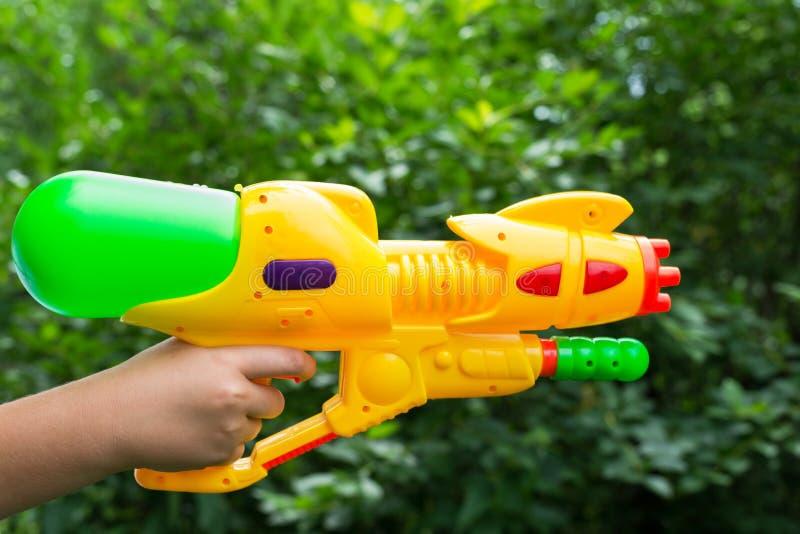 Arma de água das crianças na mão das crianças foto de stock