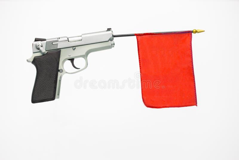 Arma de mano con una bandera roja que extiende fuera del barril Concepto fotos de archivo libres de regalías