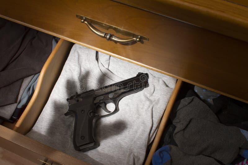Arma de mano en cajón del aparador fotografía de archivo