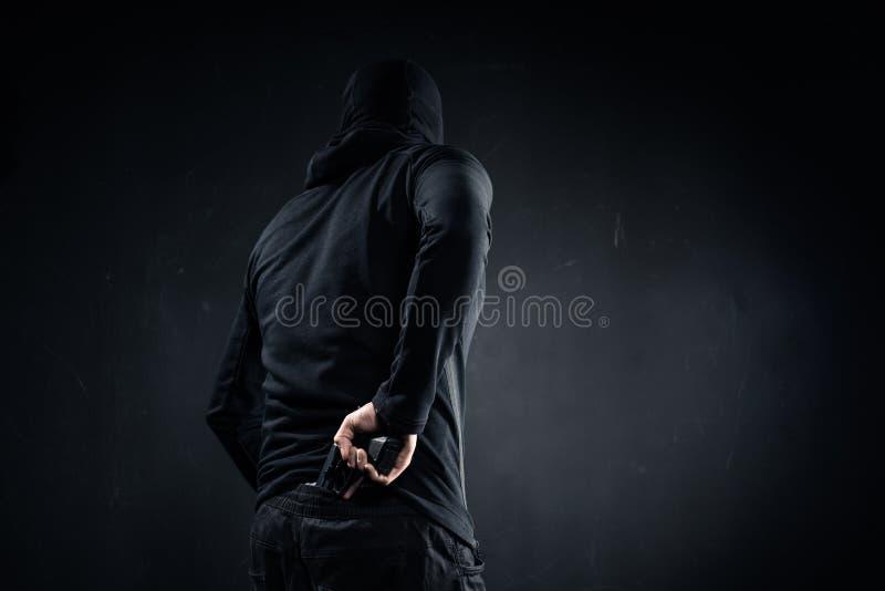 Arma de ocultación del ladrón detrás imagen de archivo libre de regalías