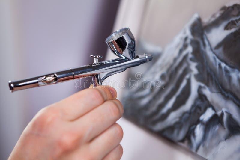 Arma de pulverização uma escova de ar na mão fêmea, montanhas de pintura com aerógrafo, fim acima da vista fotos de stock royalty free