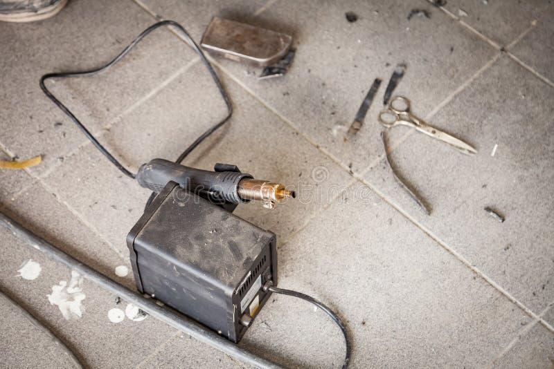 Arma de solda industrial da cor preta no assoalho entre a poeira e as ferramentas para o aquecimento e plástico de derretimento d fotografia de stock