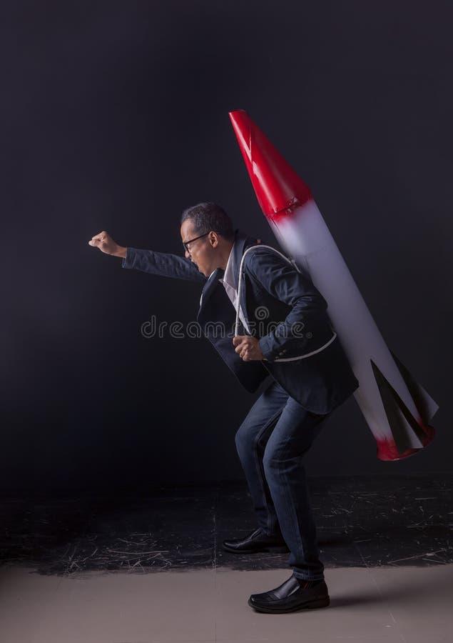 Arma di trasporto pazza del missile dell'uomo di affari che sta in perno scuro fotografia stock