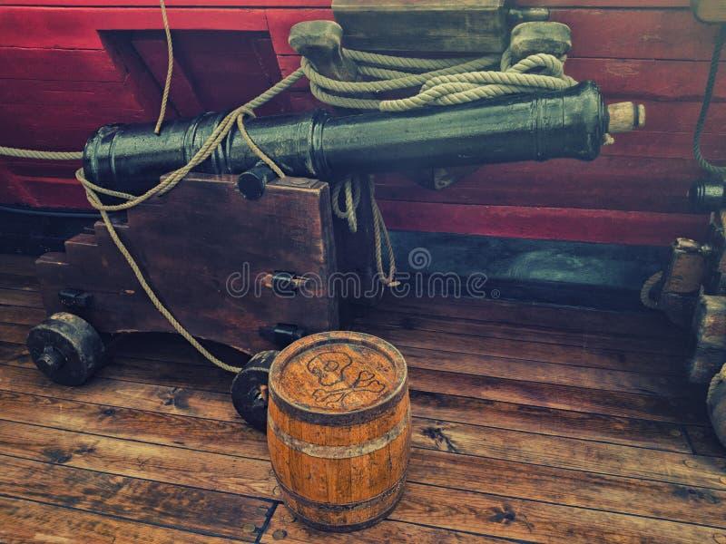 Arma e barril de pó velhos na plataforma de um navio de navigação de madeira foto de stock