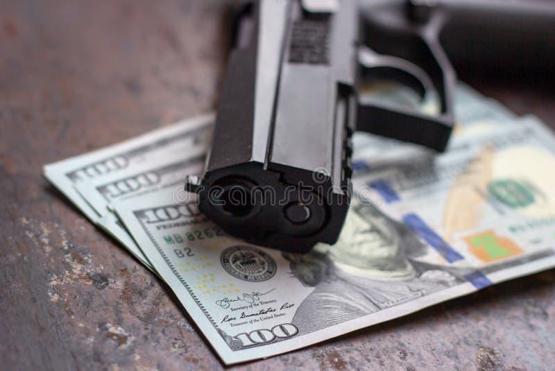 Arma negro en fondo americano de los d?lares Industria militar, guerra, comercio de armas global, venta del arma, matanza de cont imágenes de archivo libres de regalías