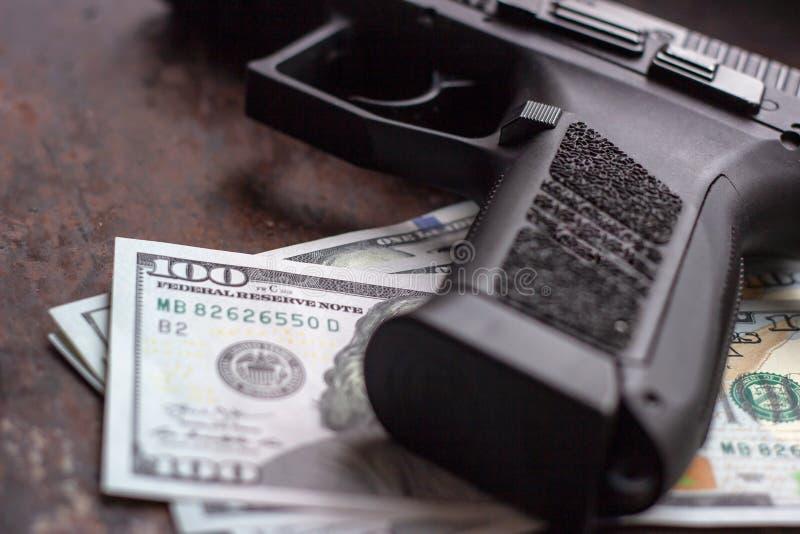 Arma negro en fondo americano de los d?lares Industria militar, guerra, comercio de armas global, venta del arma, matanza de cont foto de archivo