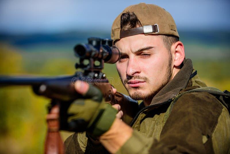 Arma o rifle del arma de la caza Cazador del hombre que apunta el fondo de la naturaleza del rifle Habilidades de la caza y equip imagenes de archivo