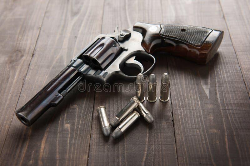 Arma preta do revólver com as balas isoladas no fundo de madeira foto de stock
