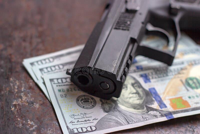 Arma preta no fundo americano dos d?lares Ind?stria militar, guerra, com?rcio de bra?os global, venda da arma, matan?a de contrat imagens de stock