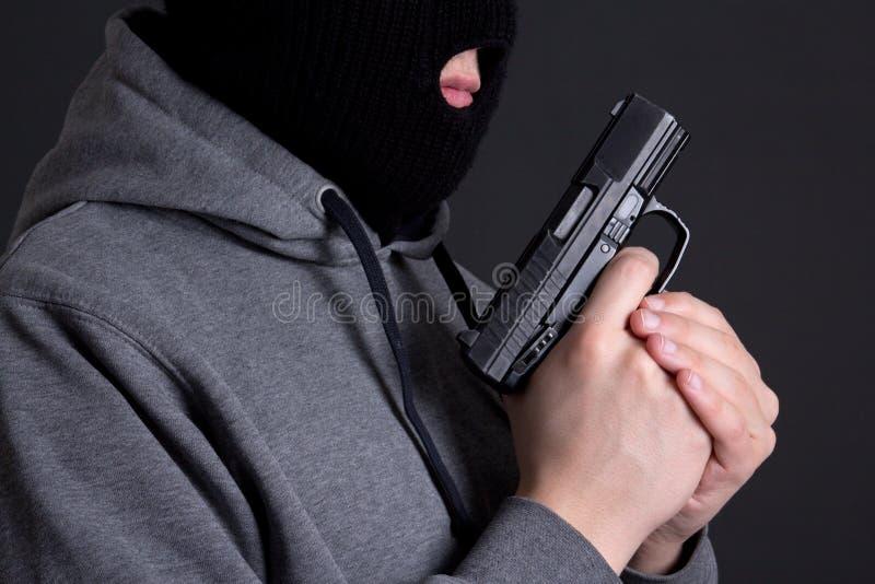 Arma que se sostiene criminal enmascarado del hombre sobre gris foto de archivo libre de regalías