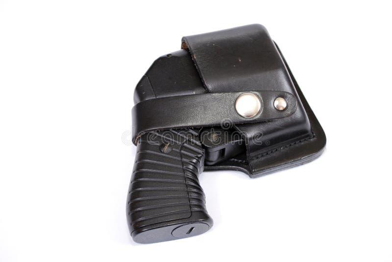 arma traumático de Cuatro-carga en una pistolera de cuero en un fondo blanco fotos de archivo