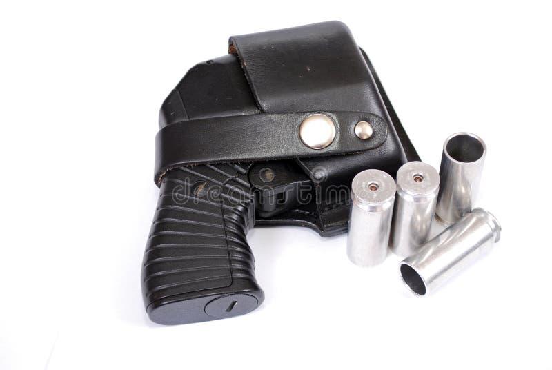 Arma traumático de cuatro-carga no cargado en una pistolera de cuero y los cartuchos que mienten cerca en un fondo blanco imagen de archivo