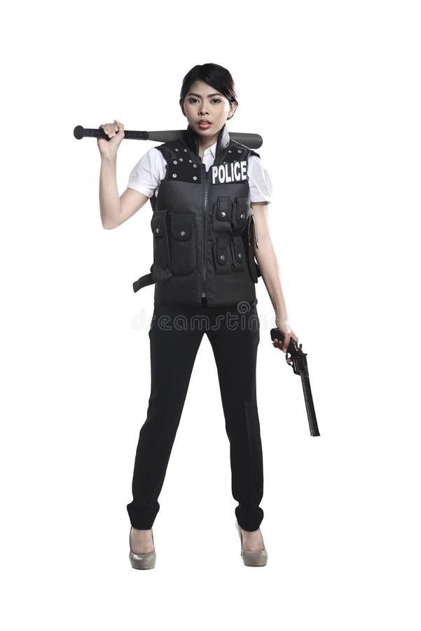Arma y bate de béisbol del revólver del control de la mujer de la policía imágenes de archivo libres de regalías