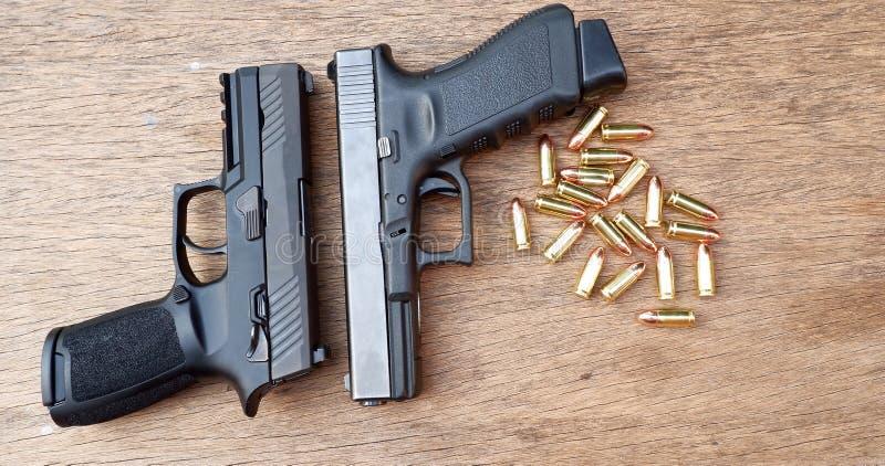 Arma y munición en fondo de madera fotos de archivo libres de regalías