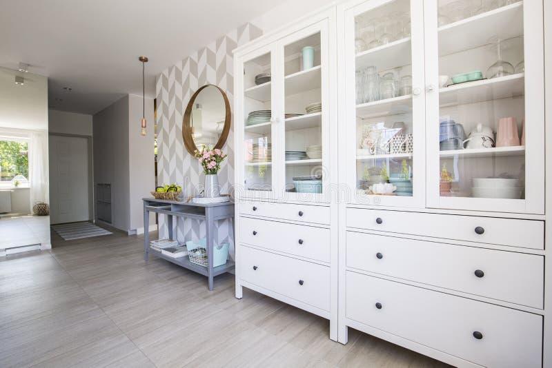 Armadietto bianco della cucina con i piatti pastelli e la tavola di console blu fotografia stock