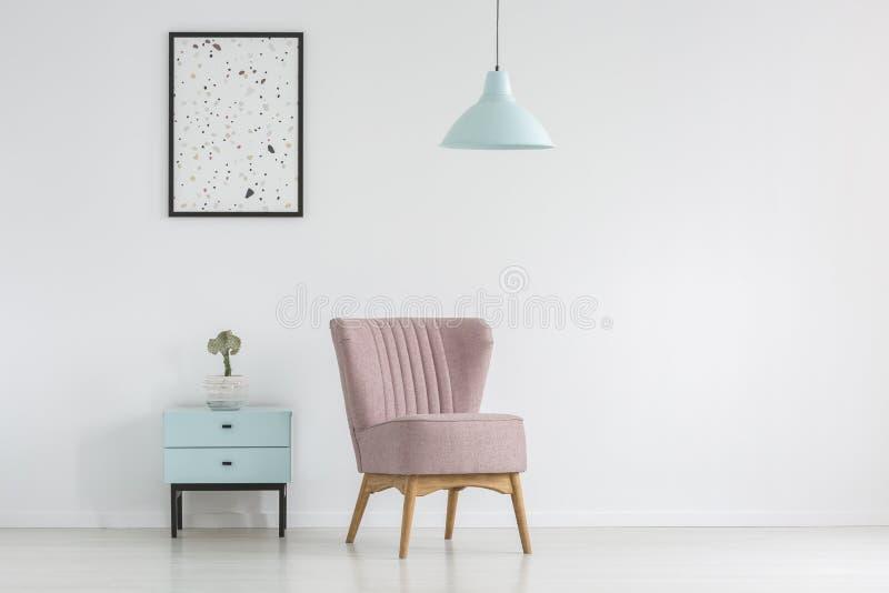 Armadietto, poltrona, manifesto e lampada su un bianco, parete vuota in a fotografie stock