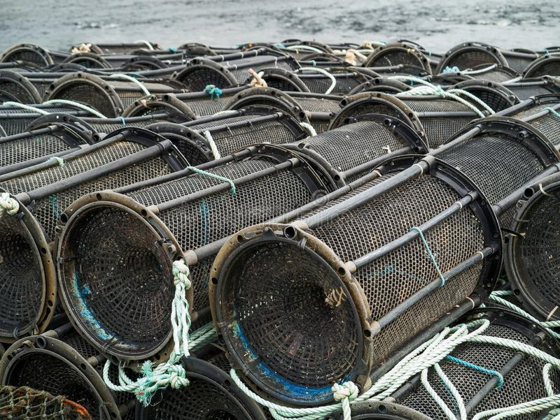 Armadilhas vazias pretas dos peixes e do caranguejo em terra, água no fundo Ind?stria de pesca imagens de stock royalty free