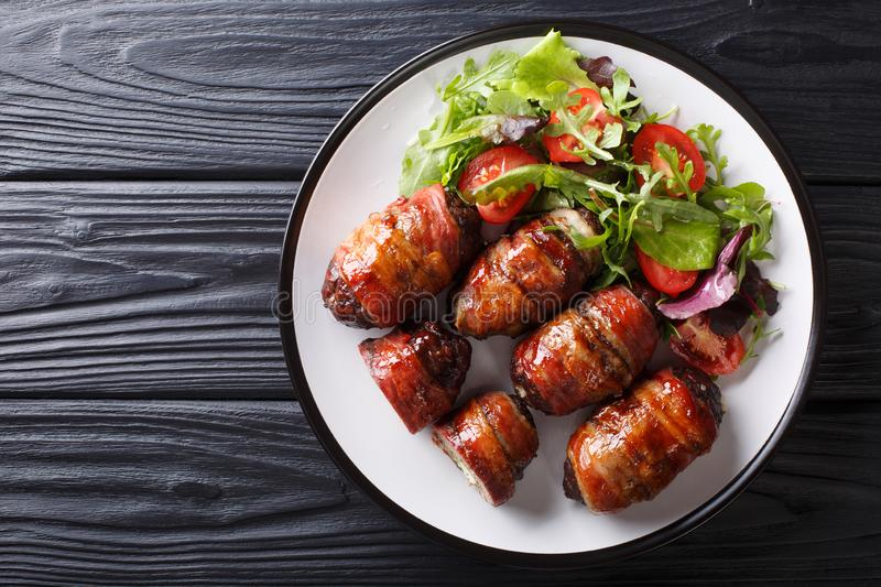 Armadillo eggs are a classic Texas BBQ staple served with salad close up on a plate. horizontal top view stock image