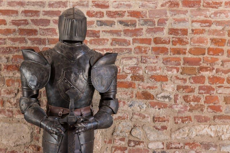 Armadura del caballero con la espada contra fondo de la pared de ladrillo foto de archivo libre de regalías
