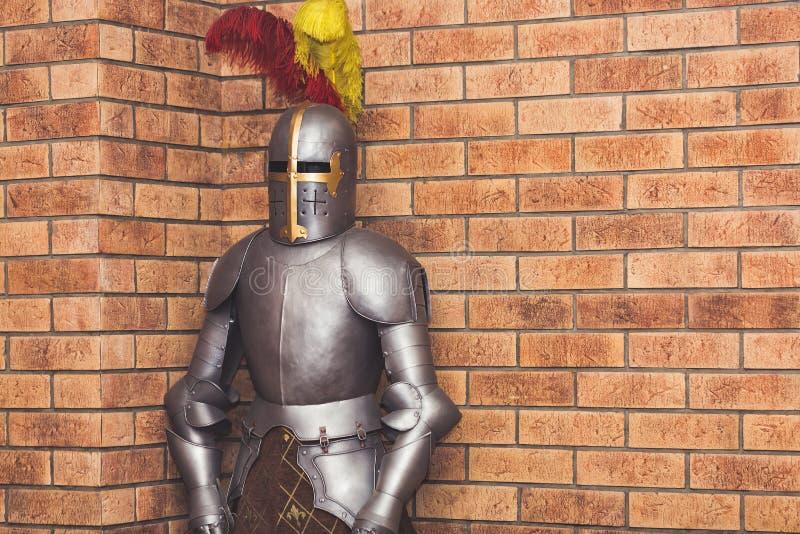 Armadura medieval do cavaleiro na perspectiva de uma parede de tijolo foto de stock