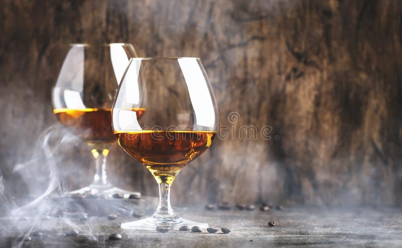 Armagnac, French grape brandy, strong alcoholic drink. Still life in vintage style with cigar smoke, copy space stock photography