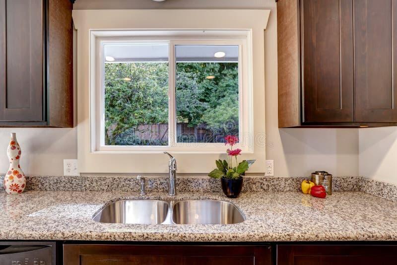 Armario de cocina con la opinión del fregadero y de la ventana fotos de archivo